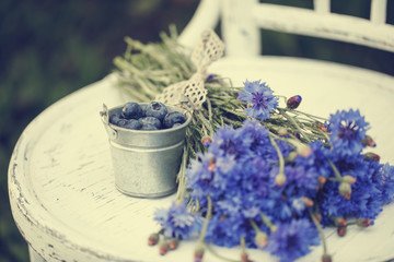 Bouquet of cornflowers and a small bucket of blueberries on the old chair in the summer garden