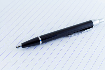 Black writing pen on paper background