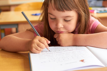 A little girl in a school class sits at a table and writes in a notebook
