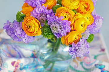 Beautiful bouquet of flowers.Yellow ranunculus flowers and scabious close-up in a glass vase on the table.