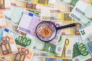 A man looks at bitcoin through a magnifying glass against the background of the euro