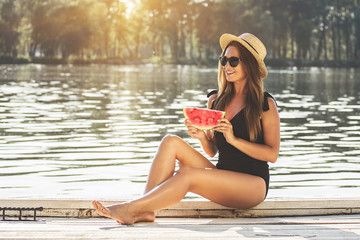 Slice of tasty watermelon. Beautiful and young woman in swimsuit and hat keeping slice of water melon in hands and looking away while sitting on wooden pier.