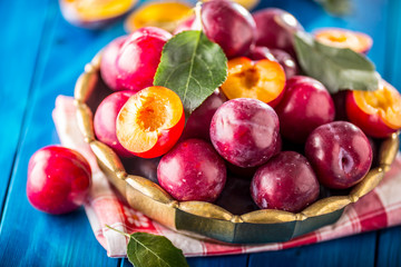 Plums. Fresh juicy plums in a bowl on a wooden or concrete board.