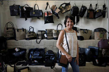 Maria Portillo de Ruffatti, owner and designer of Uca Ruffatti Manufactures, poses for a picture with her recycled tire inner tube handbags at her factory in Santa Ana