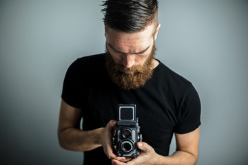 man with beard takes photo with vintage camera