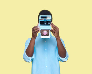 man holding instant camera, covering his face, on yellow background, conceptual