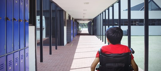 Composite image of rear view of boy sitting in wheelchair
