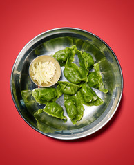 gyoza with ginger in metal bowl, on red background, studio