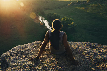 Young man hipster with long hair sitting at cliff edge and looking at sunset and nature, view from back