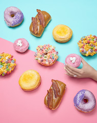 gourmet donuts with hand in-frame, on pink and turquoise background, studio