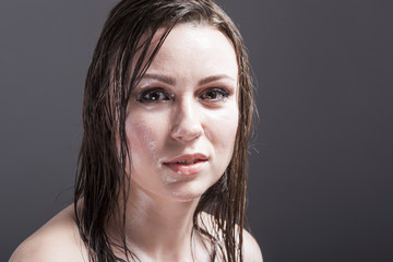 Beauty Concepts and Ideas. Closeup Portrait of Caucasian Sensual Brunette Showing Wet and Shining Skin and Wet Hair. Against Dark Grey Background.