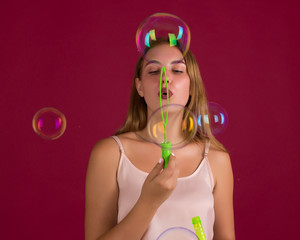 Young cute girl blows bubbles, pretty woman