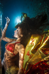 Beautiful bright shot brunette underwater in red slik dress