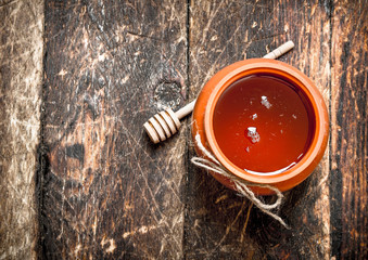 Wall Mural - Honey pot with a wooden spoon.