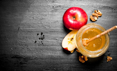 Wall Mural - Honey background. Honey in pot with slices of ripe apples and nuts.