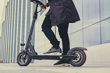 Close up image of a man on an electric scooter. Wall mural