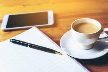 on wooden table in  coffee shop interior near mobile phone and cup of  coffee book pen and smartphone.