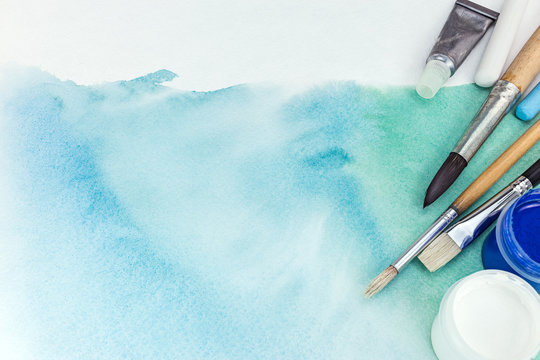 artist paintbrushes and paints over abstract hand painted watercolor background on textured paper