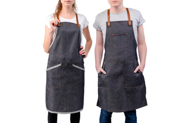 Young chefs or waiters man and woman posing, wearing aprons isolated on white background. Barista cafe coffee uniform. - fototapety na wymiar
