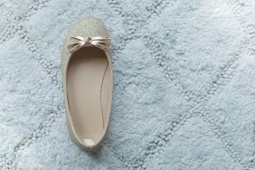 a cute golden sparkling ballet shoe of little girl on green pastel rug, filtered tones