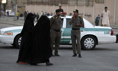 Women walk past members of Saudi security forces as they keep guard in Manfouha, southern Riyadh