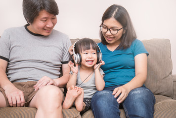 Asian parents and baby girl in sofa using tablet and headphones