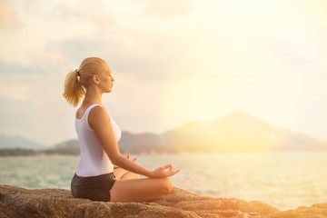 Young woman is practicing yoga on a stone at tropical sea sunrise background.