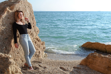 Young woman on sand sea coast leaning against big rock and looking at sand lost in thoughts. Sea on background.