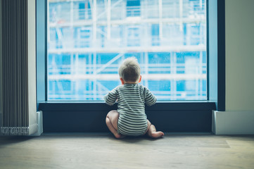 Little baby by window in high rise apartment