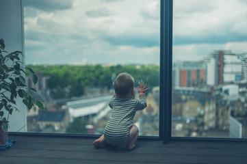 Little baby sitting on balcony in the city