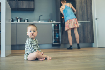 Little baby on kitchen floor with mother in background