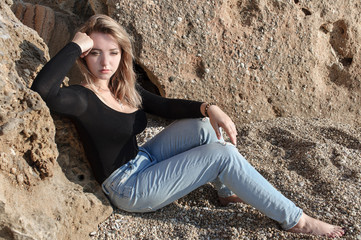 Dreamily young woman relaxing at sea coast leaning against big rock and looking far lost in thoughts.