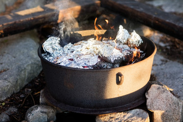 Food Wrapped In Foil Being Cooked On Firepit