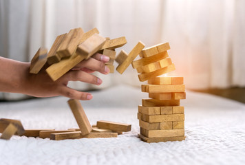 Young man pulling out wood block fail on building tower at home and drape change, choice business risking dangerous project plan failure construction