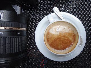 Cropped view from above over a work space with professional camera and camera lens and white coffee on black metal table