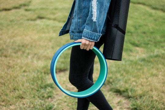 girl with yoga wheel and yoga mat