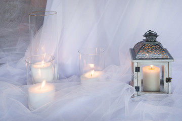 lanterns with candles on white silk background
