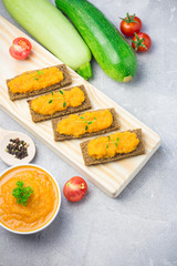 Vegetable marrow spread on toasted bread with vegetable caviar. Top view, copy space.