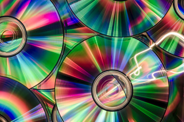 background of cds or dvds with shiny colorful reflection