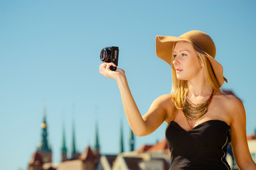 Beautiful elegant woman taking pictures with camera