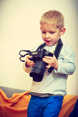 Kid playing with big professional digital camera