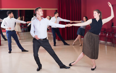 Young people dancing lindy hop in pairs