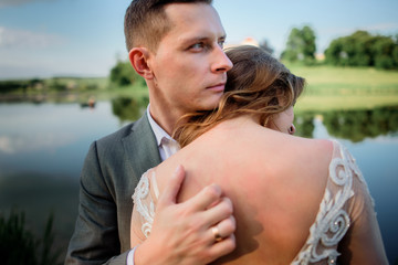 Beautiful newlyweds pose before an old castle on green grass