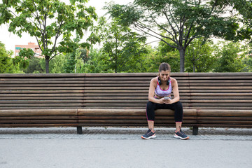 Pretty fit young woman listening to music on park bench.