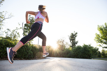 Back view of fit woman running and exercising in sunlight in the park.