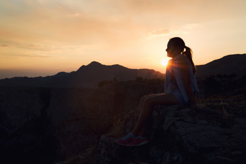 Girl looking at sunset on mountain