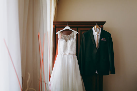 Wedding dress of the bride and groom's suit hang in the room