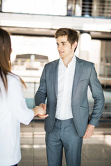 Businessman and Businesswoman shaking hands in office. Business concept