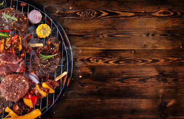 Photo on textile frame Grill / Barbecue Top view of fresh meat and vegetable on grill placed on wooden planks