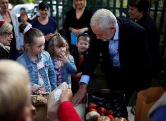 Britain's opposition Labour party leader, Jeremy Corbyn, helps fill childrens packed lunches outside the Hope Centre in Bolton